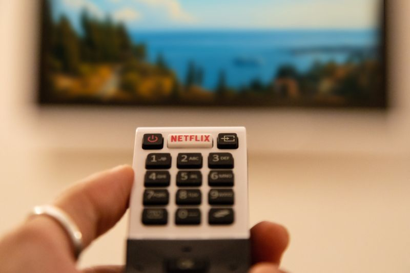 Ortigia, Italy - August 23, 2018: A hand holding television remote control with dedicated Netflix button in front of defocused smart tv