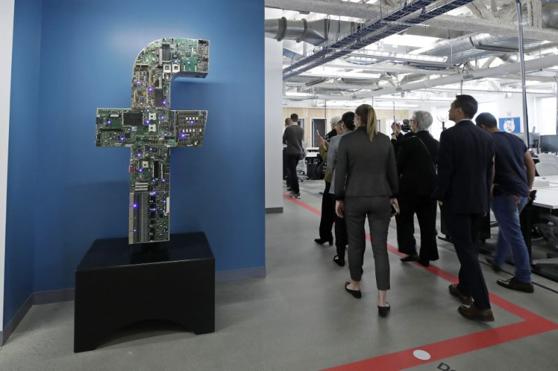 """FILE - In this Jan. 9, 2019, file photo, media and guests tour Facebook's new 130,000-square-foot offices, which occupy the top three floors of a 10-story Cambridge, Mass., building. Facebook, which perfected what critics call """"surveillance capitalism,"""" knows it has serious credibility issues. Those go beyond repeated privacy lapses to include serious abuses by Russian agents, hate groups and disinformation mongers, which Mark Zuckerberg acknowledged only belatedly. (AP Photo/Elise Amendola, File)"""