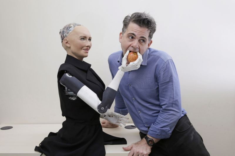 """In this Sept. 28, 2017, photo, David Hanson, the founder of Hanson Robotics, poses with his company's flagship robot Sophia, a lifelike robot powered by artificial intelligence in Hong Kong. Sophia is a creation of the Hong Kong-based startup working on bringing humanoid robots to the marketplace. Hanson envisions a future in which AI-powered robots evolve to become """"super-intelligent genius machines"""" that can help solve mankind's most challenging problems. (AP Photo/Kin Cheung)"""
