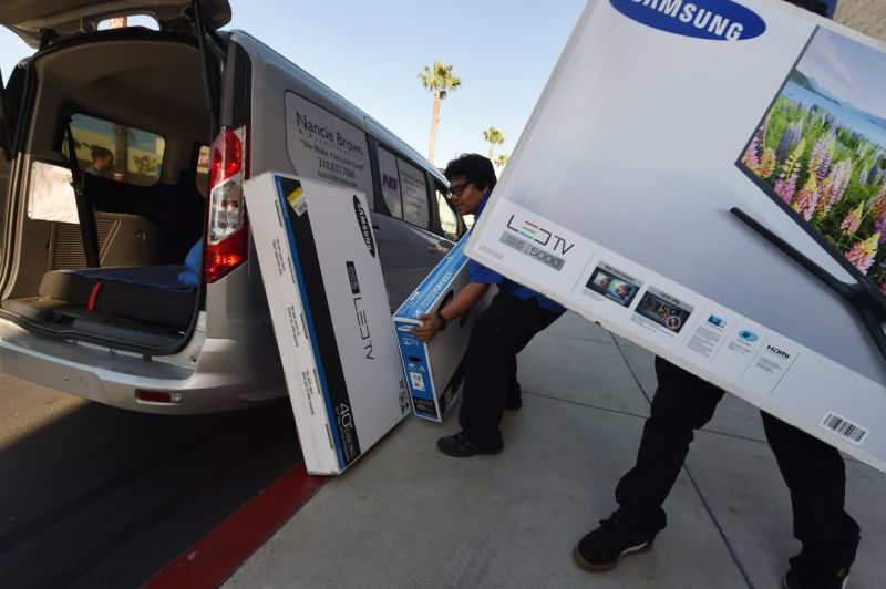 """Best Buy staff load a television during a Black Friday sale in Los Angeles, California on November 27, 2015. The US holiday shopping season kicks off with """"Black Friday"""" -- the day after the Thanksgiving holiday -- with a frenzy expected at stores around the country as retailers slash prices. AFP PHOTO/ MARK RALSTON / AFP / MARK RALSTON (Photo credit should read MARK RALSTON/AFP via Getty Images)"""
