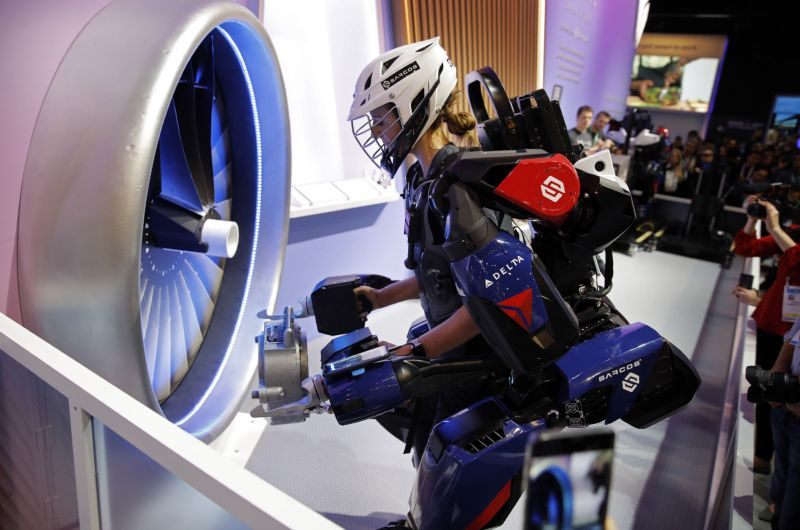 Tara Scranton demonstrates the Sarcos Robotics Guardian XO at the Delta Airlines booth during the CES tech show, Wednesday, Jan. 8, 2020, in Las Vegas. The full-body powered exoskeleton is designed to boost the user's strength and endurance. (AP Photo/John Locher)