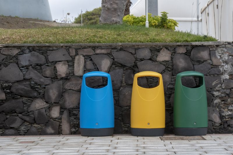 Recycling bins near a stone wall